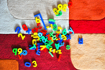 Play with letters on a colorful carpet