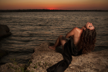 brunette woman on the sunset background  with a black cloth