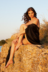 brunette woman on the sunset covered with a black cloth