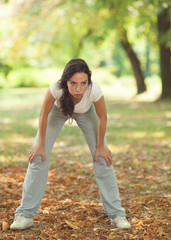 Young woman resting after exercising in a park