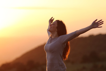 Woman at sunset breathing fresh air raising arms