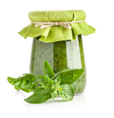 Basil and Glass jar of pesto sauce isolated on white