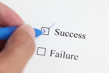 """Hand with ballpoint pen marking the """"SUCCESS"""" checkbox"""
