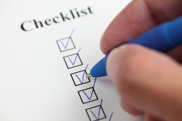Hand filling a checklist