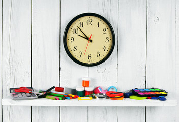Watches and school tools on a wooden shelf.
