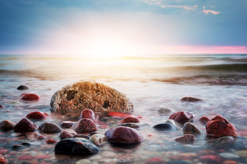 Dramatic colorful sunset on a rocky beach. Baltic sea