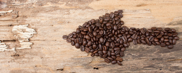 Arrow from the coffee beans on wood background
