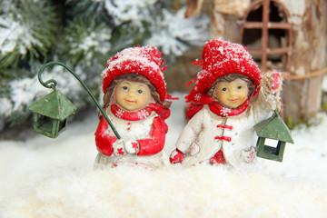 Kinder mit Laternen sitzen im Schnee