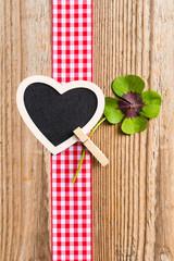 Holzhintergrund mit Herztafel und vierblättrigem Kleeblatt