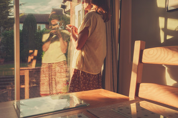 Young woman standing by french doors at sunset