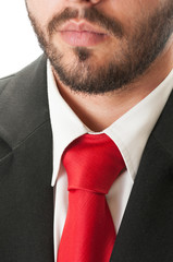 Black suit, red tie and beard.