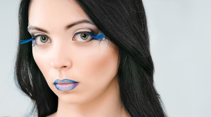 Beautiful female face with blue fashion make-up