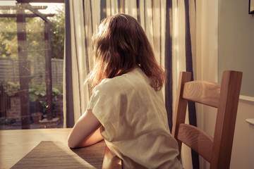 Young woman sitting at table and looking out the window