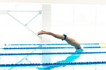 Young swimmer jumping from starting block
