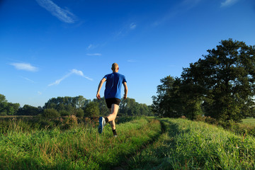 Man trailrunning in the countryside on a sunny morning.