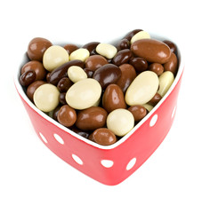 chocolate covered nuts and raisins in a heart-shaped bowl