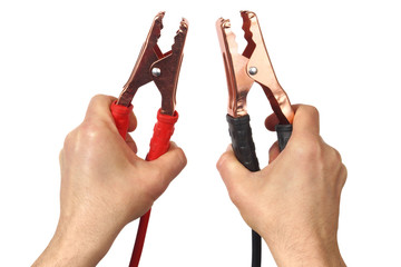 Hands with jumper cables on white