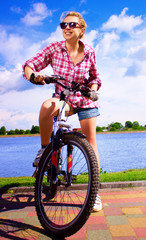 Young happy woman is sitting on her bicycle, outdoor shoot