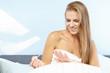 beautiful woman applying red nail polish in bed at home