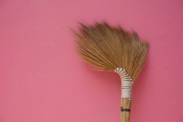 Brown broom on pink concrete gray wall