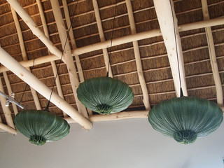 Modern design wooden ceiling. Green chandeliers in the shape of