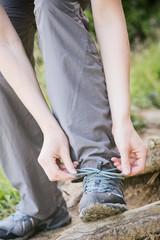 Woman Ties Shoe on Trail