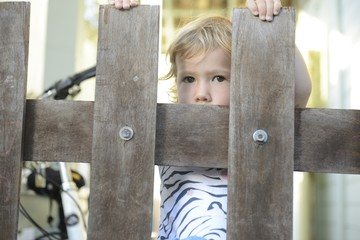 Baby girl looking through bars of wooden fence