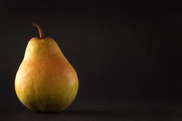 Beautiful ripe yellow pear on black background