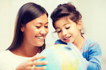 mother and daughter with globe