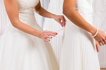 Brides at wedding dress fitting in shop