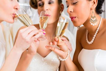 Brides drinking champagne in wedding shop