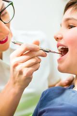 Zahnärztin behandelt Junge in Zahnarztpraxis