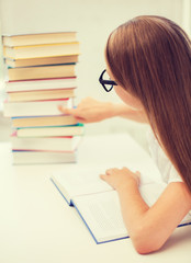 little student girl in eyeglasses with many books