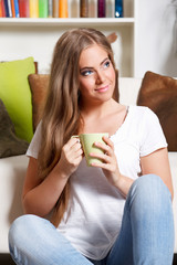 Beautiful young woman holding a cup of drink in the living room