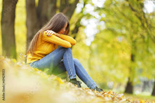 canvas print picture Woman sitting on autumn leaves
