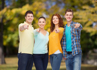 group of smiling teenagers pointing fingers on you