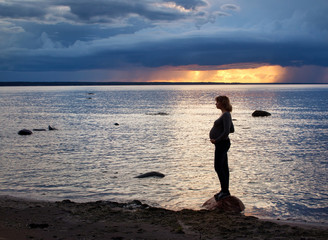 Pregnant woman at sunset