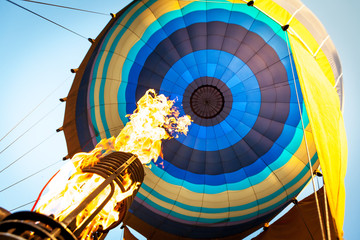 Hot air from a gas burner fills the dome of the balloon
