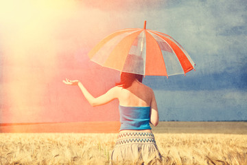 Redhead girl with umbrella at field