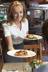 Waitress Serving Customer Sitting At Table In Restaurant