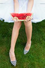 Girl with watermelon sitting on a garden bench