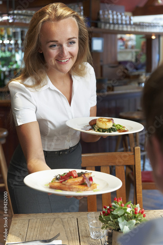 canvas print picture Waitress Serving Customer Sitting At Table In Restaurant