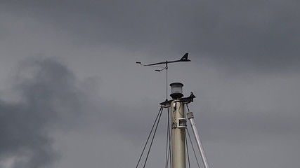 Marine weather wind vane on top of a sail boat mast