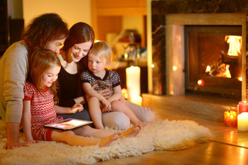Happy young family using a tablet pc at home by a fireplace