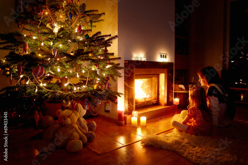 canvas print picture Young mother and her daughter by a fireplace
