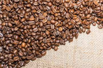 roasted coffee beans background on burlap texture