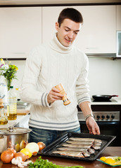 Handsome man adding spices in raw fish