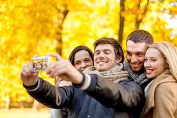 group of smiling men and women making selfie