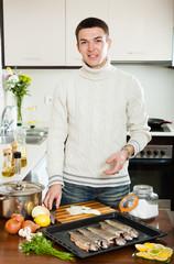 Handsome man cooking  fish  in baking sheet