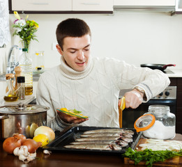 guy cooking  fish with lemon in baking sheet